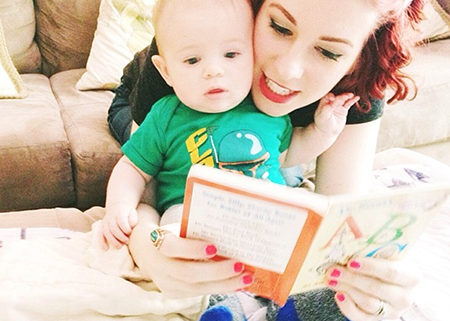 An adult and baby playing speech games at home