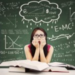 Stressed Asian student in a classroom. Shot against blackboard with formulas