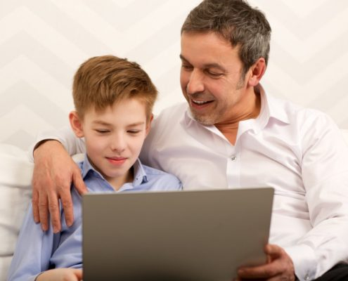 father and son who has expressive language disorder on a laptop