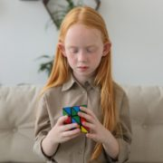 a child playing with a rubik's cube to help promote her speech therapy at home