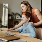 a parent helping their child learn at home online during the pandemic