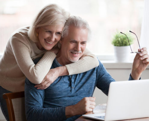 a man with Parkinson's at home on his laptop with his wife next to him