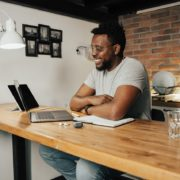 African-American adult sitting at desk using laptop