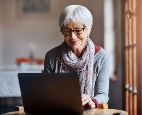 a woman on a laptop with Parkinson's Disase