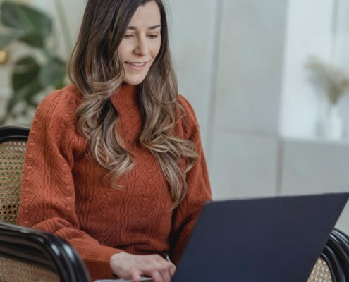 a woman researching the difference between a stutter and stammer from her laptop at home
