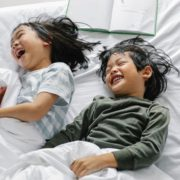A boy and girl at home laughing and speaking to each other