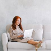 A woman researching Huntington's disease symptoms from her couch at home