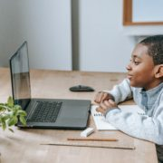 a 5 year old child at a laptop learning at home